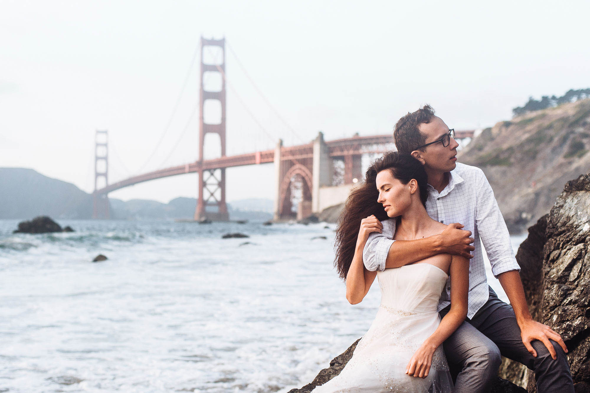 san francisco after wedding photo session couple sitting at beach hugging main